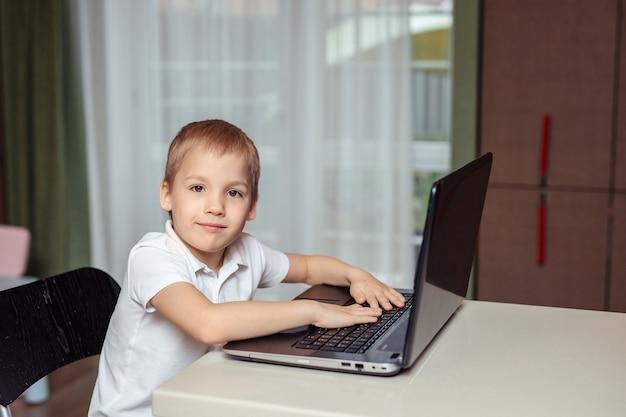 Domowe Nauczanie Na Odległość Dzieci Podczas Kwarantanny. Szczęśliwy Chłopca W Białym Polo Odrabiania Lekcji Za Pomocą Laptopa Siedząc W Domu W Kuchni Premium Zdjęcia