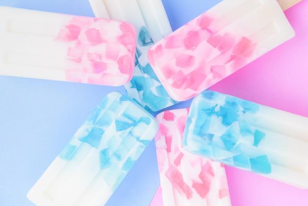 Domowe patyczki do lodów, popsicle, pop pop lub zamrażarka na niebieskim i różowym pastelowym tle Premium Zdjęcia