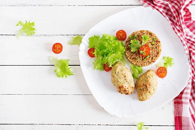 Domowe Pieczone Kotlety Z Ryżem Na Stole W Stylu Rustykalnym. Zdrowe Jedzenie. Widok Z Góry Premium Zdjęcia