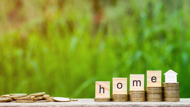 Domowe słowo na stosie monet i stos złotych monet na drewnianym stole. Premium Zdjęcia