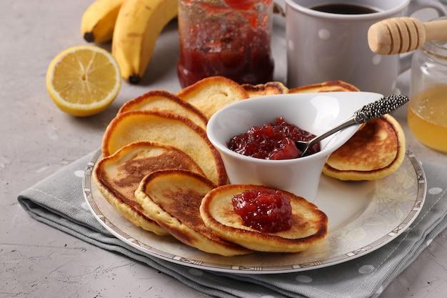Domowe śniadanie Naleśniki Z Dżemem, Miodem, Bananami I Filiżanką Kawy Na Szarej Serwetce Na Betonowym Tle Premium Zdjęcia