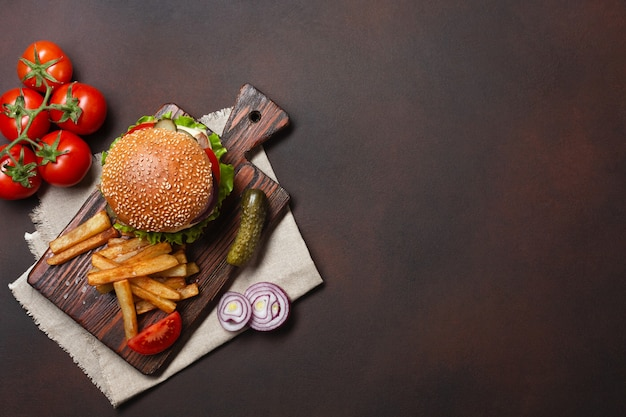 Domowy Hamburger Ze Składnikami Wołowiny, Pomidorów, Sałaty, Sera, Cebuli, Ogórków I Frytek Na Desce Do Krojenia Premium Zdjęcia