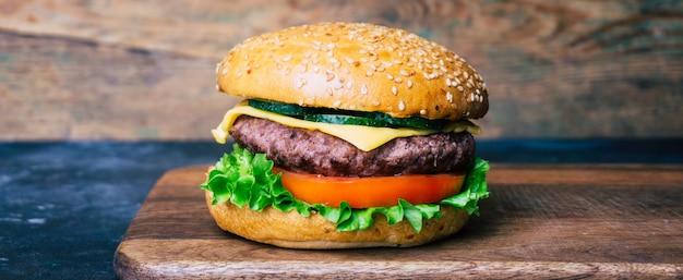 Domowy robić hamburger z wołowiną na drewnianym tle (cheeseburger). klasyczny domowy burger. Premium Zdjęcia