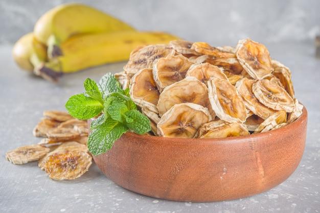 Domowy Suszony Banan, Ekologiczne Chipsy Bananowe W Drewnianej Misce Premium Zdjęcia