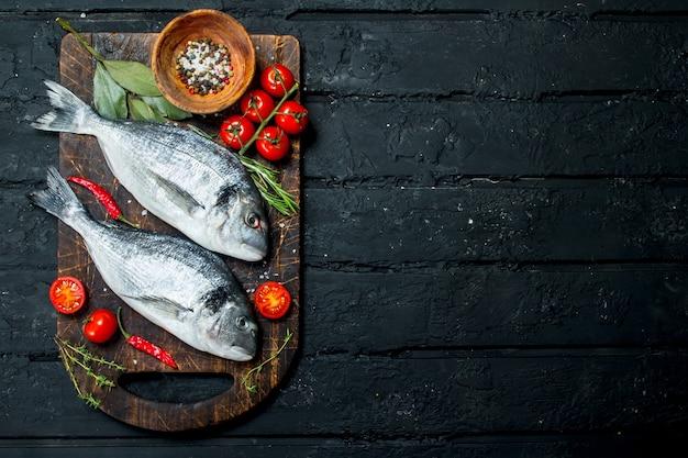 Dorado Z Surowej Ryby Morskiej Z Pomidorami, Ziołami I Przyprawami. Na Czarnym Tle Rustykalnym. Premium Zdjęcia