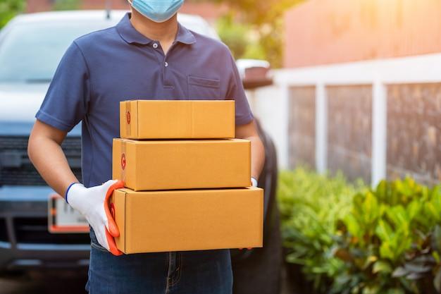 Doręczeniowy Azjatykci Mężczyzna Trzyma Kartony W Medycznych Gumowych Rękawiczkach I Masce. Zakupy Online I Dostawa Ekspresowa Lub E-commerce. Koncepcja Zapobiega Rozprzestrzenianiu Się Zarazków I Zapobiega Infekcjom Covid-19 Premium Zdjęcia