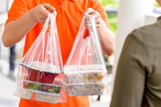 Doręczeniowy Mężczyzna W Pomarańczowym Mundurze Dostarcza Azjatyckie Pudełka Do żywności W Plastikowych Torbach Klientowi W Domu Premium Zdjęcia