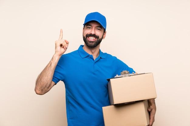 Doręczeniowy mężczyzna z brodą nad odosobnioną ścianą wskazuje w górę doskonałego pomysłu Premium Zdjęcia
