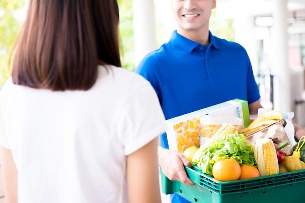 Doręczyciel dostarcza produkty spożywcze kobiecie Premium Zdjęcia