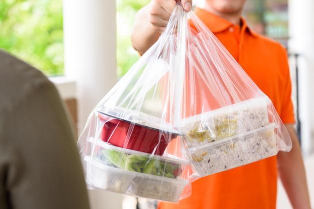Doręczyciel Podający Lunch Box W Workach Do Cutomer, Który Zamówił Online W Domu Premium Zdjęcia