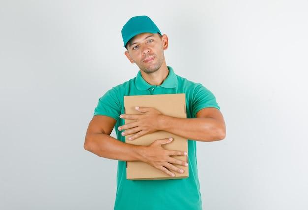 Doręczyciel Przytulający Karton W Zielonej Koszulce Z Czapką Darmowe Zdjęcia