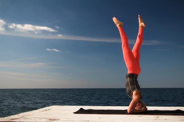 Dorosła blond kobieta z krótką fryzurą ćwiczy jogę na molu Premium Zdjęcia