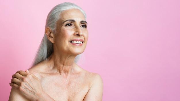 Dorosła kobieta ono uśmiecha się na różowym tle Darmowe Zdjęcia