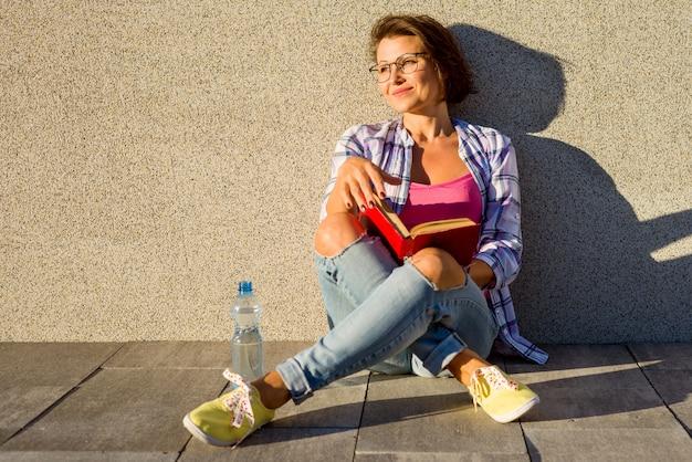 Dorosła Kobieta Relaksuje Siedzieć Na Chodniczku Premium Zdjęcia