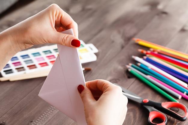 Dorosła Kobieta Robi Origami łódce Premium Zdjęcia