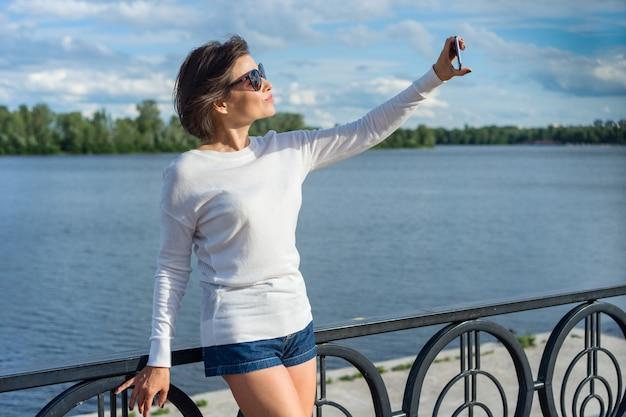 Dorosła Kobieta Robi Selfie Za Pomocą Telefonu Premium Zdjęcia