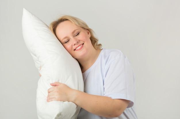 Dorosła Kobieta W Białej Koszulce Z Poduszką Premium Zdjęcia
