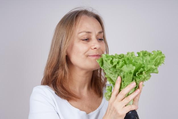 Dorosła Kobieta W Białej Koszuli Trzyma Bukiet Zielonej Sałatki Premium Zdjęcia