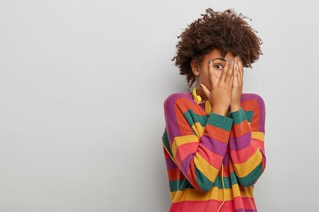 Dorosła Kobieta Z Fryzurą Afro, Patrzy Przez Palce, Zakrywa Twarz Obiema Rękami, Nosi Słuchawki I Sweter W Paski, Stoi Na Tle Białego Studia Darmowe Zdjęcia