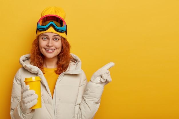 Dorosła Snowboardzistka O Rudych Włosach, Lubi Gorące Napoje Zimą, Nosi Odzież Narciarską, Wskazuje Na Wolne Miejsce Na Treści Promocyjne Lub Tekst. Darmowe Zdjęcia
