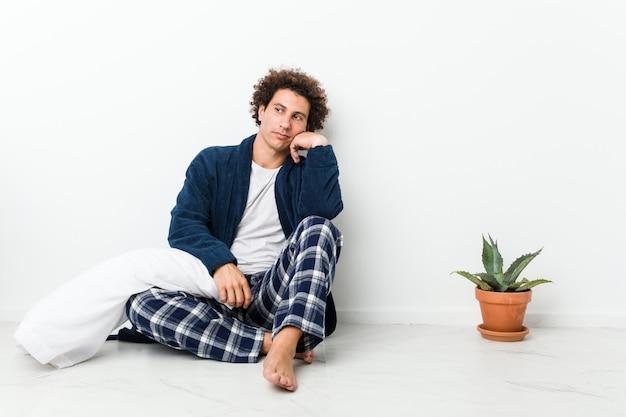 Dorośleć Mężczyzna Jest Ubranym Piżamy Obsiadanie Na Domowej Podłoga Która Czuje Smutny I Zadumany, Patrzejący Kopii Przestrzeń. Premium Zdjęcia