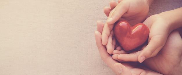 Dorosły i dziecko ręce holiding czerwony on, on koncepcja zdrowia i darowizny Premium Zdjęcia