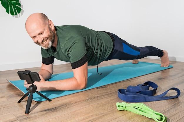 Dorosły Kaukaski Mężczyzna W Odzieży Sportowej Robi Deskę Na Macie Przed Smartfonem Podczas Treningu Online. Premium Zdjęcia