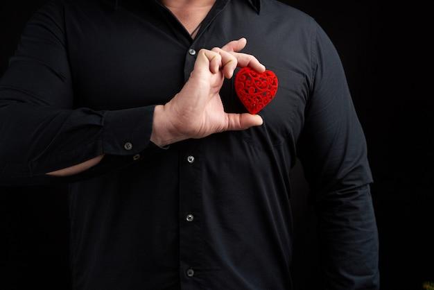 Dorosły Mężczyzna Stoi Na Ciemności W Czarnej Koszuli I Trzyma Czerwone Rzeźbione Serce Przy Piersi Premium Zdjęcia