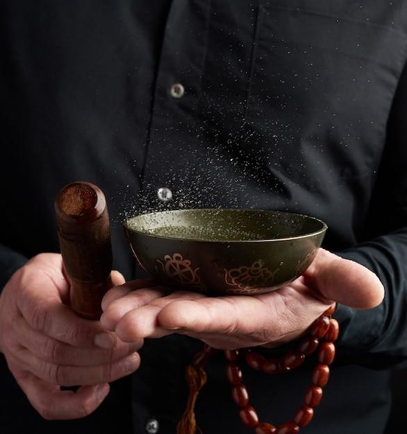 Dorosły Mężczyzna W Czarnej Koszuli Obraca Drewniany Patyk Wokół Miedzianej Tybetańskiej Miski Z Wodą. Rytuał Medytacji Premium Zdjęcia