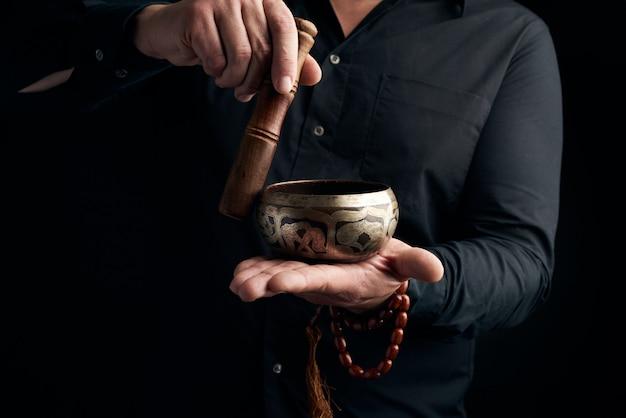 Dorosły Mężczyzna W Czarnej Koszuli Obraca Drewniany Patyk Wokół Miedzianej Tybetańskiej Miski Z Wodą Premium Zdjęcia