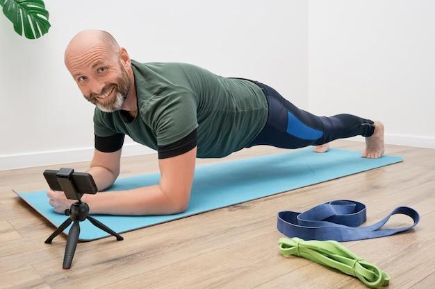 Dorosły Mężczyzna W Odzieży Sportowej Wykonuje ćwiczenia Na Macie Przed Smartfonem Podczas Treningu Online. Premium Zdjęcia