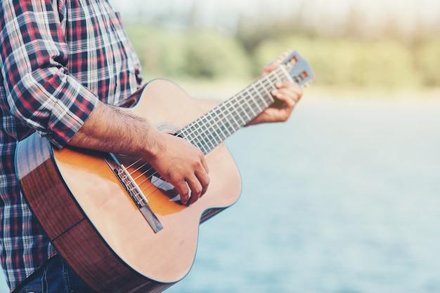 Dorosły przystojny muzyk grający na gitarze akustycznej Darmowe Zdjęcia