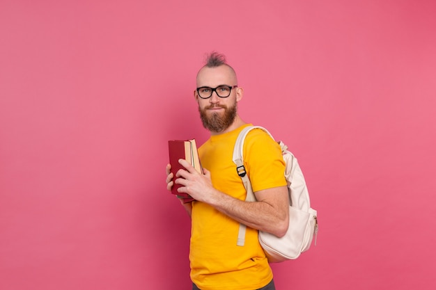 Dorosły Student Wesoły Facet Na Co Dzień Z Brodą I Plecakiem Trzymając Książki Na Różowym Tle Darmowe Zdjęcia