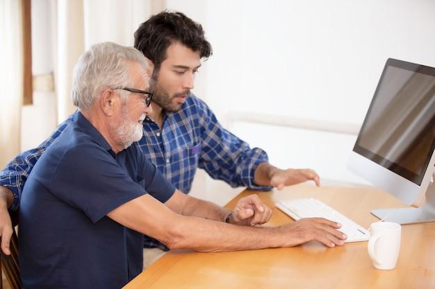 Dorosły Syn Hipster I Starszy Ojciec Spędzają Razem Czas W Domu, Rozmawiając, Dbając O Ojca I Używając Komputera. Premium Zdjęcia