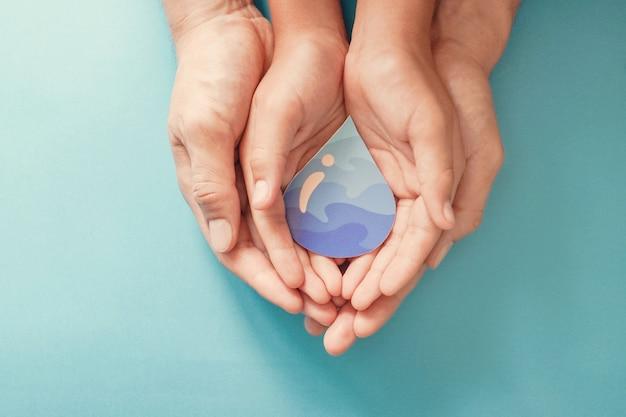 Dorosłych I Dzieci Ręce Trzymając Papier Wyciąć Kropla Wody. światowy Dzień Wody. Czysta Woda I Urządzenia Sanitarne, Csr, Oszczędzaj Wodę. Premium Zdjęcia