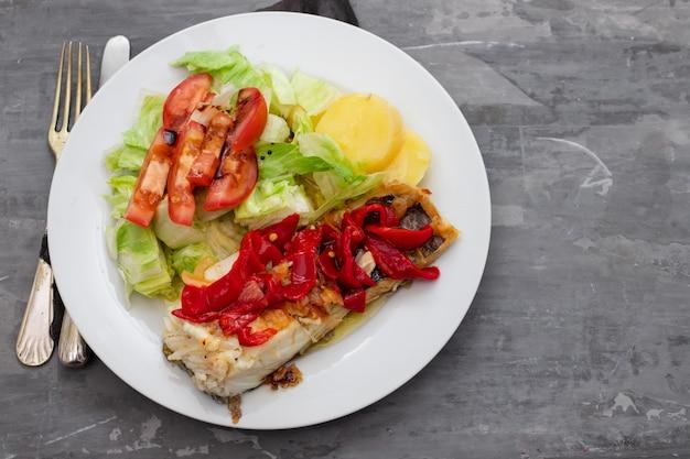 Dorsz Z Czerwoną Papryką, Ziemniakami I Sałatą Na Białym Talerzu Na Ceramicznym Tle Premium Zdjęcia