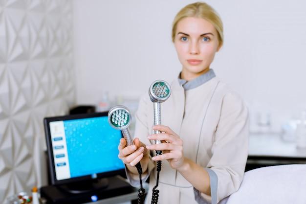 Dość Blond Kobieta Kosmetolog Kosmetyczka I Kosmetyczka Trzyma Narzędzie Do Mezoterapii Led Photon Terapia światłem Rf Odmładzanie Skóry, Stojąc W Salonie Kosmetycznym Lub Klinice. Premium Zdjęcia