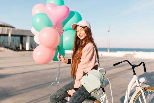 Dość Długowłosa Dziewczyna W Różowym Stroju Siedzi Na Rowerze Z Balonami Czekając Na Przyjaciela Z Rejsu. Darmowe Zdjęcia