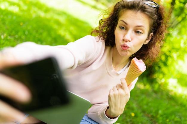 Dość Młoda Kaukaska Kobieta Jest Niezależna W Parku Z Laptopem, Filiżanką Kawy I Lodów, Siada Na Trawie I Robi Selfie Premium Zdjęcia