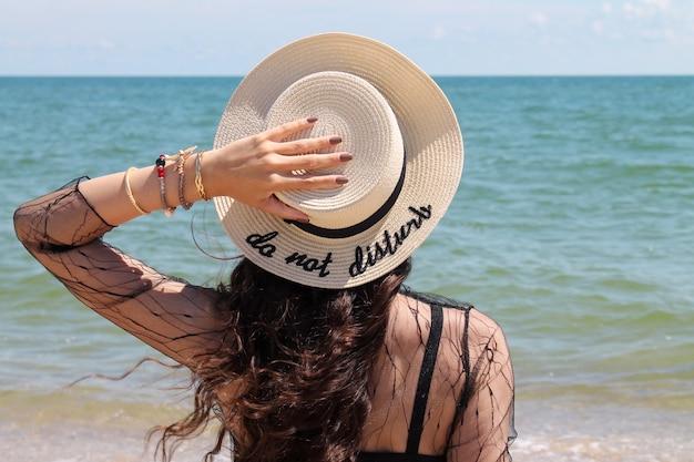 Dość Młoda Kobieta W Letnie Wakacje Na Sobie Słomkowy Kapelusz Z Widokiem Na Ocean Premium Zdjęcia