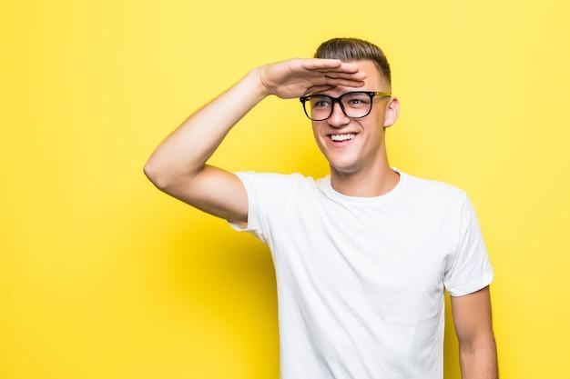 Dość Młody Chłopak Z Niecierpliwością Oczekuje Ubrany W Białą Koszulkę I Przezroczyste Okulary Na żółtym Tle Darmowe Zdjęcia