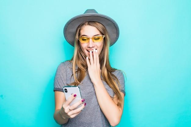 Dość Młody Model Moda T-shirt, Kapelusz I Okulary Przezroczyste Z Telefonem W Dłoniach Na Białym Tle Na Zielonym Tle Darmowe Zdjęcia