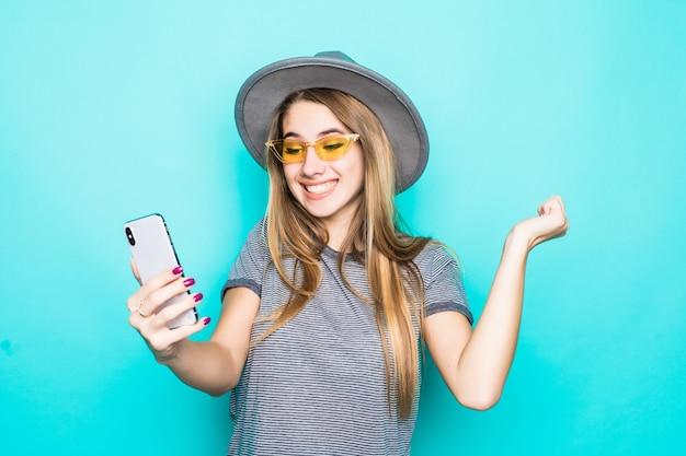 Dość Młody Model W T-shirt Moda, Kapelusz I Okulary Przezroczyste Z Telefonem W Dłoniach Sprawia, że Selfie Na Białym Tle Na Zielonym Tle Darmowe Zdjęcia