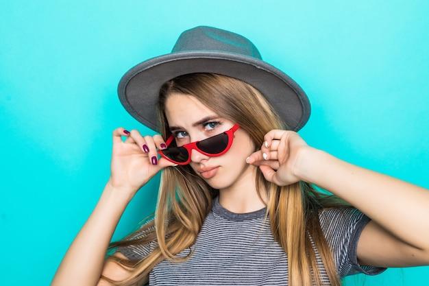 Dość Młody Model Ze Złotymi Włosami W Moda T-shirt, Kapelusz I Przezroczyste Okulary Na Białym Tle Na Zielonym Tle Darmowe Zdjęcia