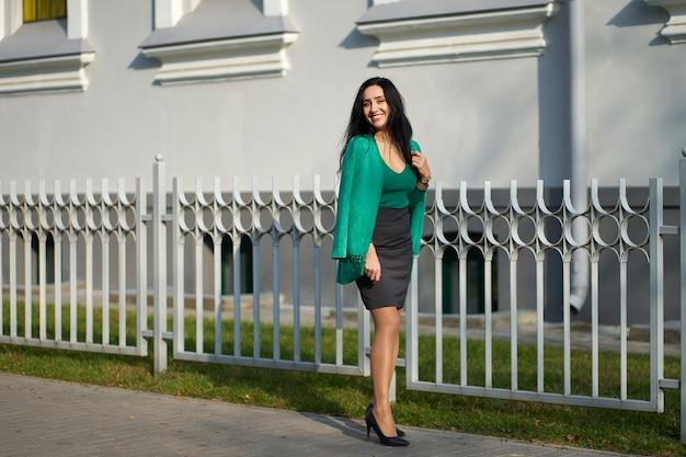 Dość Smilling Brunetka Dziewczyna Ubrana W Szarą Spódnicę, Zielony Sweter I Stylową Zieloną Kurtkę Pozowanie Na Kamery Premium Zdjęcia