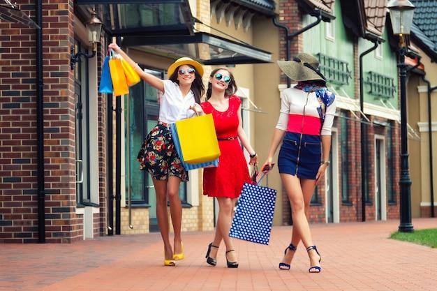 Dość szczęśliwy jasnych kobiet kobiet dziewczyn przyjaciół w kolorowe sukienki, czapki i buty na obcasie z torby na zakupy chodzenia po ulicy po zakupach Premium Zdjęcia