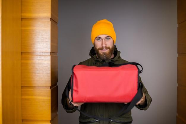 Dostarcz Mężczyznę W Masce Medycznej Obsługującej Papierowe Pudełko Z Pizzą W środku, Daj Klientowi W Drzwiach Darmowe Zdjęcia