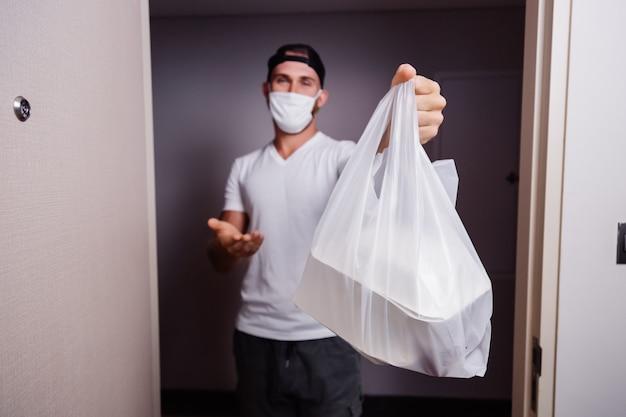 Dostarcz Mężczyźnie Trzymającemu Plastikową Torbę Z Jedzeniem Darmowe Zdjęcia