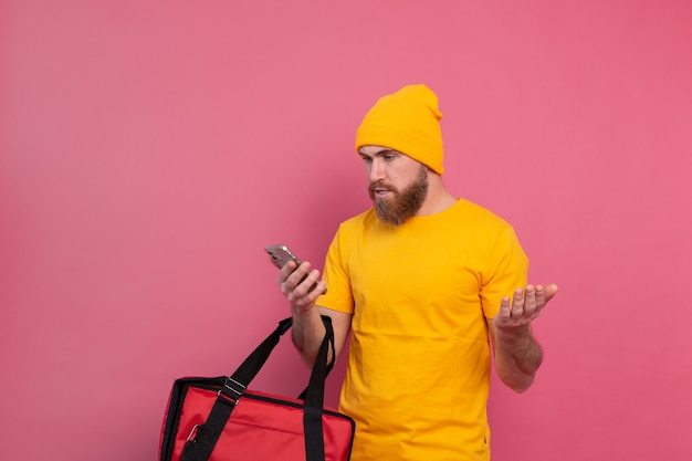 Dostarczając Jedzenie Z Oburzeniem Niezadowolony Patrząc Na Telefon Na Różowo Darmowe Zdjęcia