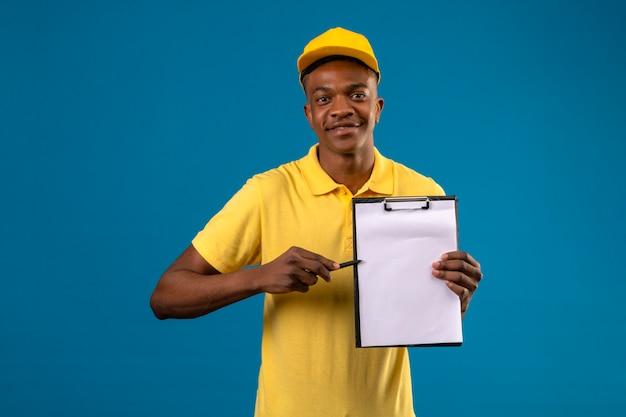 Dostawa Afroamerykanin Człowiek W żółtej Koszulce Polo I Czapce, Trzymając Schowek Z Pustymi Miejscami, Wskazując Piórem Na Nim Uśmiechnięty Przyjazny Stojący Na Niebiesko Darmowe Zdjęcia
